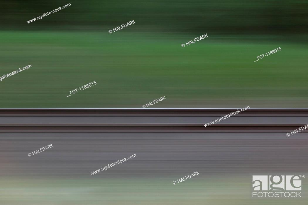 Stock Photo: Railroad tracks and grass seen in blurred abstract pattern from moving train.