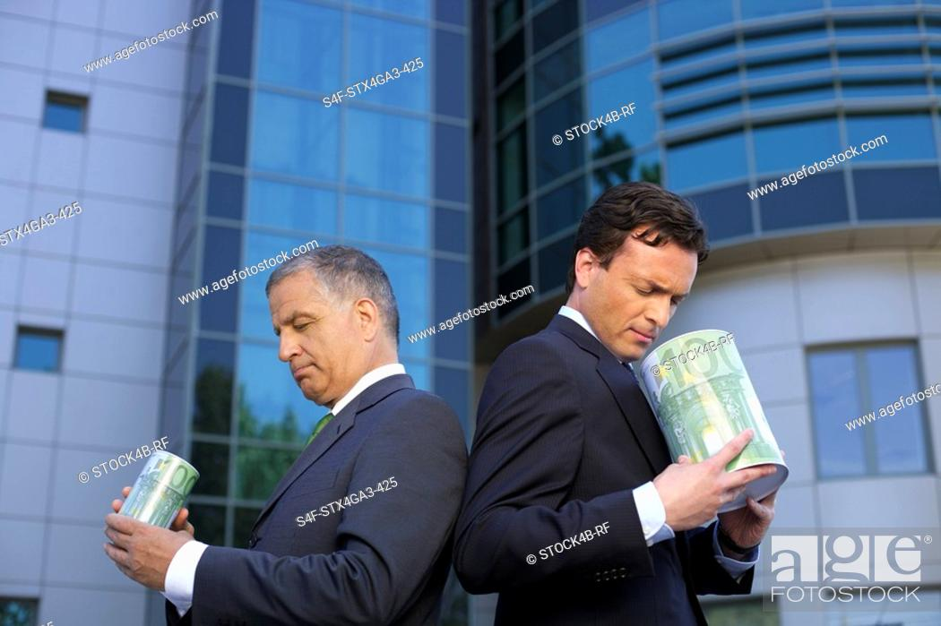Stock Photo: Two Businessman standing back to back with cylinders in their hands.