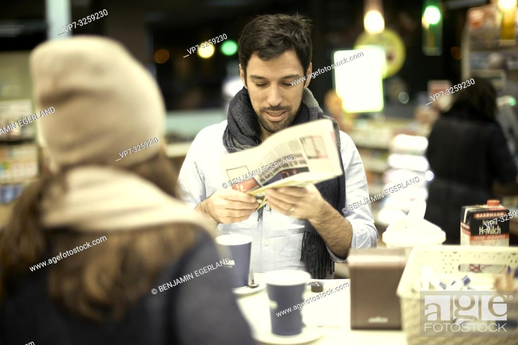 Stock Photo: man looking at newspapers in hands, in coffee shop, couple, in Munich, Germany.