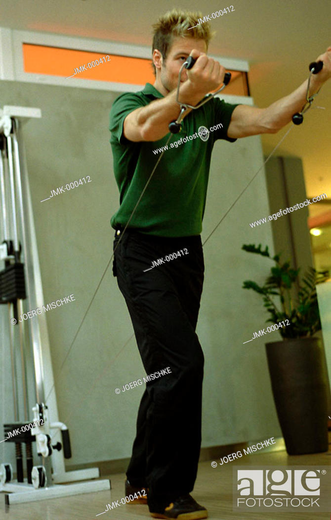 Stock Photo: Young man at the fitness studio, gym, working out, doing exercises.