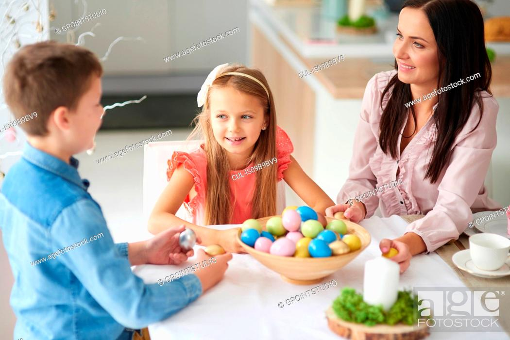 Stock Photo: Girl with brother and mother preparing colourful easter eggs at dining table.