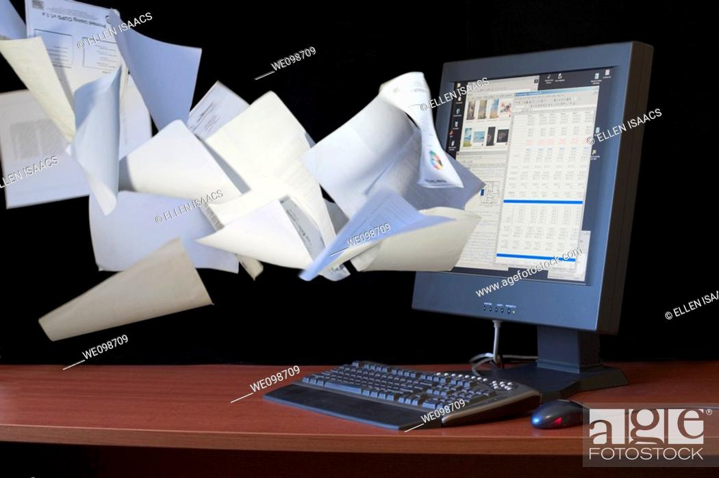 Stock Photo: Papers flying into a flat screen computer monitor  Indicates the idea of the paperless office, suggesting how computers can help people organize their work and.