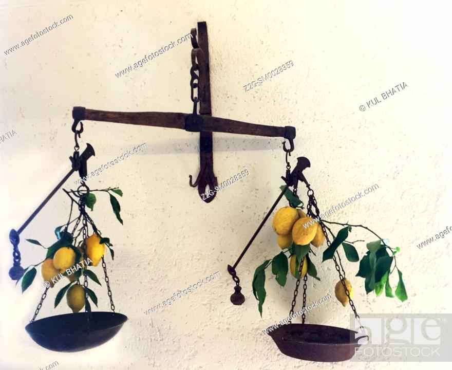 Stock Photo: Fresh lemons hanging from old-style balances at a farm store, an iconic image of the Amalfi Coast. The farm grows vegetables, fruits.