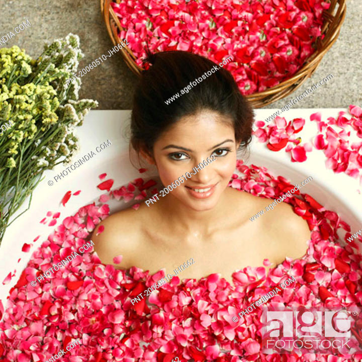 Stock Photo: High angle view of a young woman in a bathtub full of rose petals.