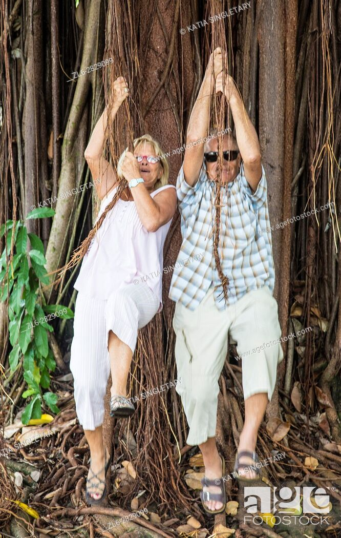 Stock Photo: Older, mature couple , retired, playing tarza and jane hanging, having fun hanguing from a tree, and walking hand in hand in a distillery.