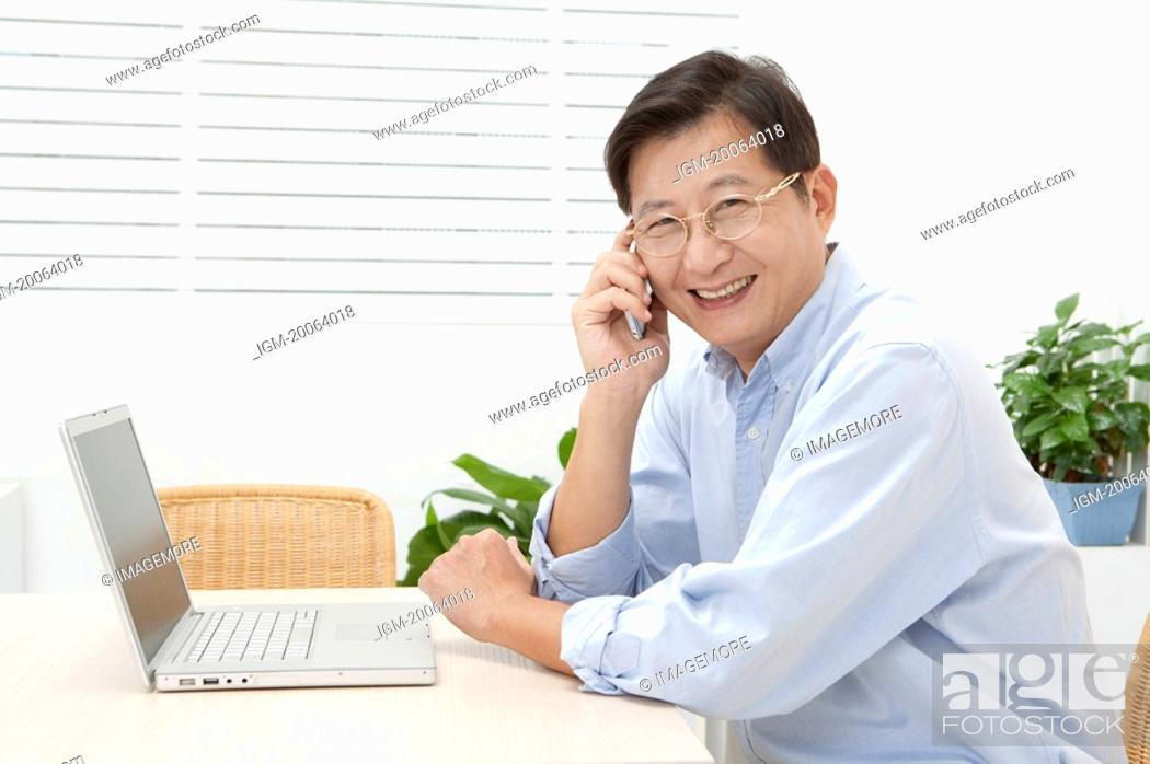 Stock Photo: Husband, Man using mobile phone and smiling at the camera.