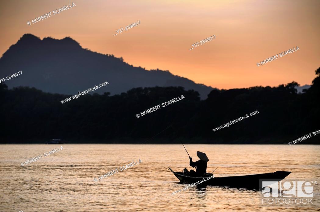 Stock Photo: Asia. South-East Asia. Laos. Province of Luang Prabang, city of Luang Prabang, World heritage of UNESCO since 1995. Fisherman on Mekong river.