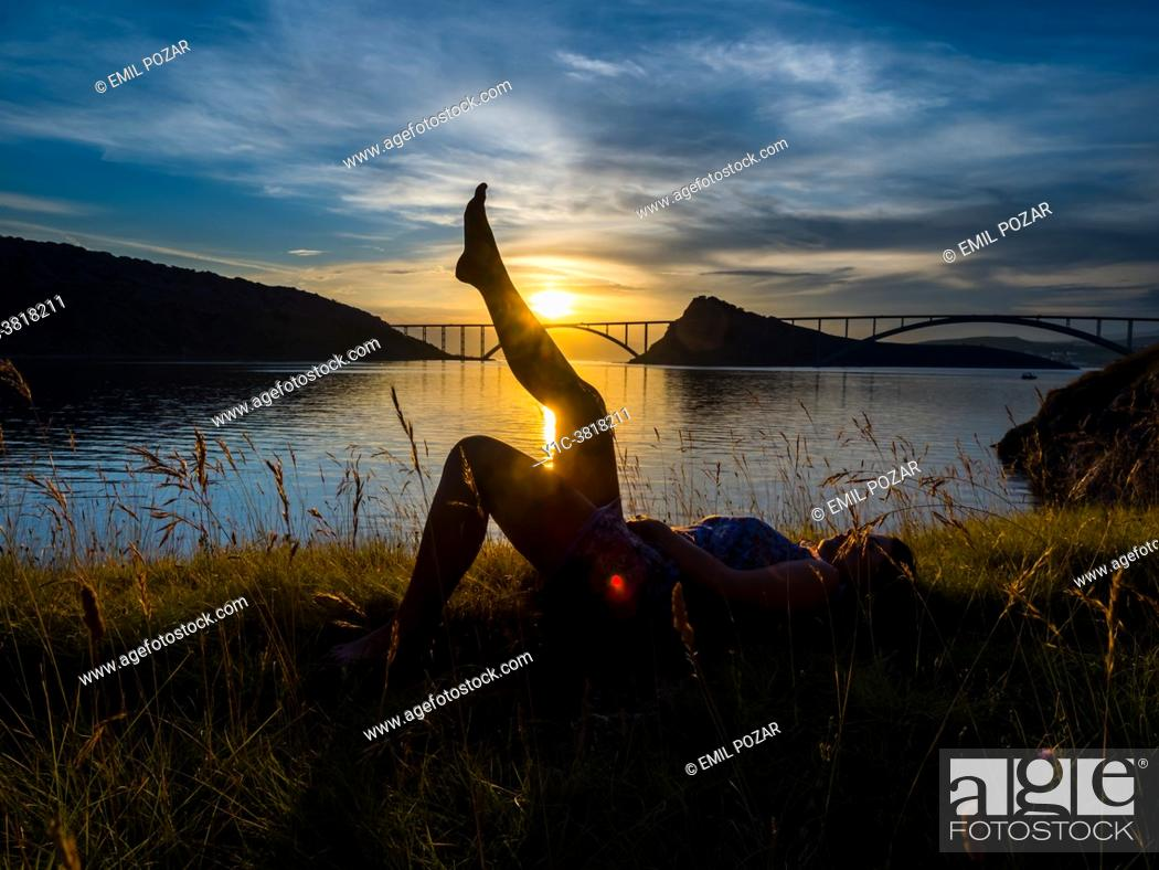 Stock Photo: Young woman sunset silhouette raised legs.