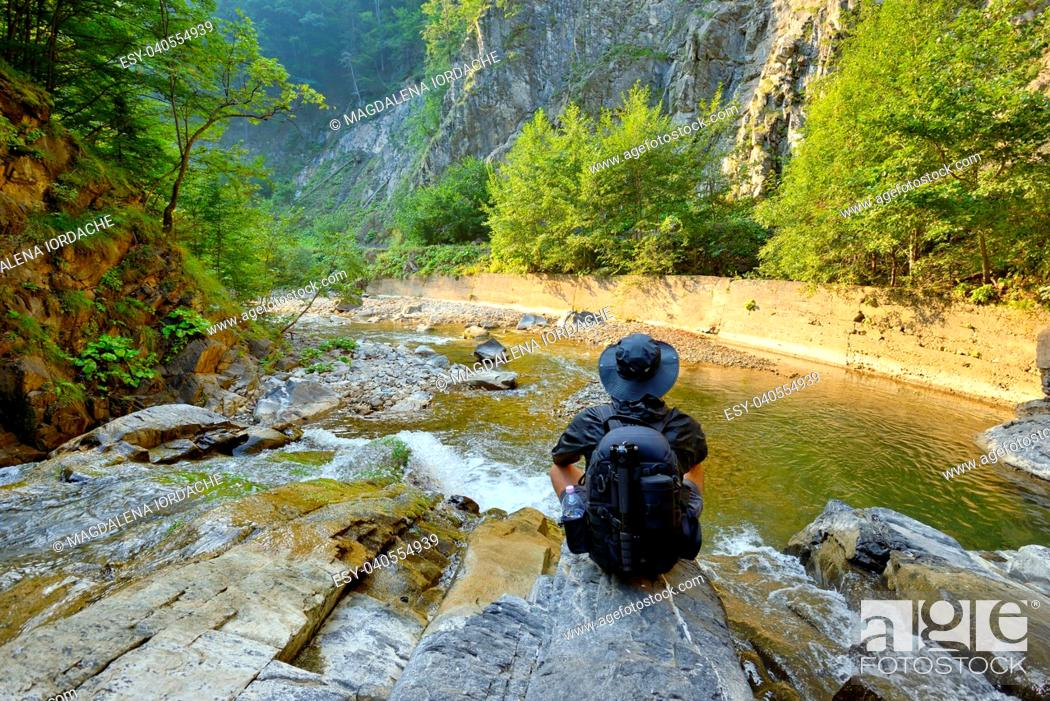 Stock Photo: young man with backpack enjoying on mountain and waterfall.