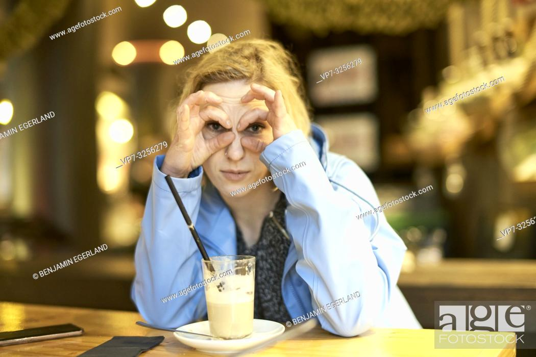 Stock Photo: woman shaping rings around eyes, sitting in café, in Munich, Germany.