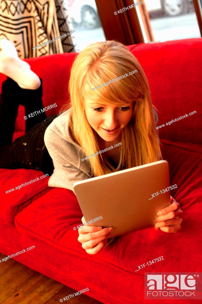 Stock Photo: A fourteen year old teenage girl using a digital tablet to read Facebook and email at home, UK.