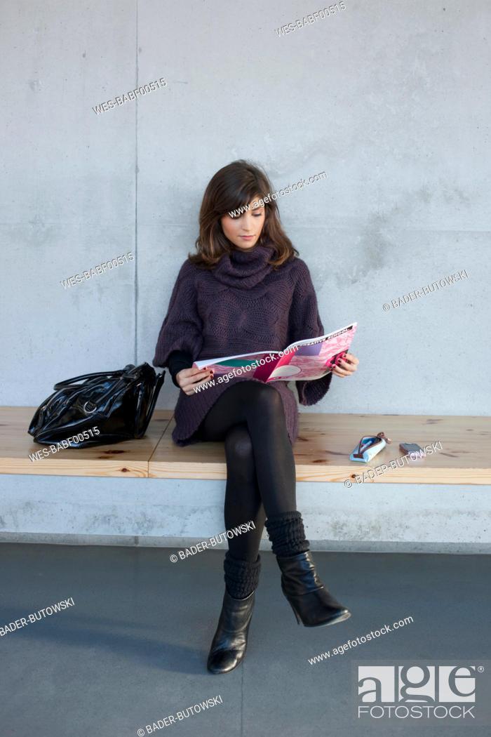 Stock Photo: Germany, Leipzig, Woman sitting and reading magazine.