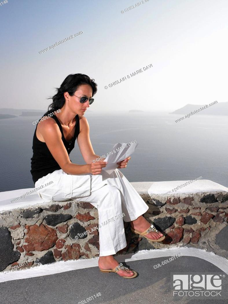 Stock Photo: Woman reading a letter on a low wall.