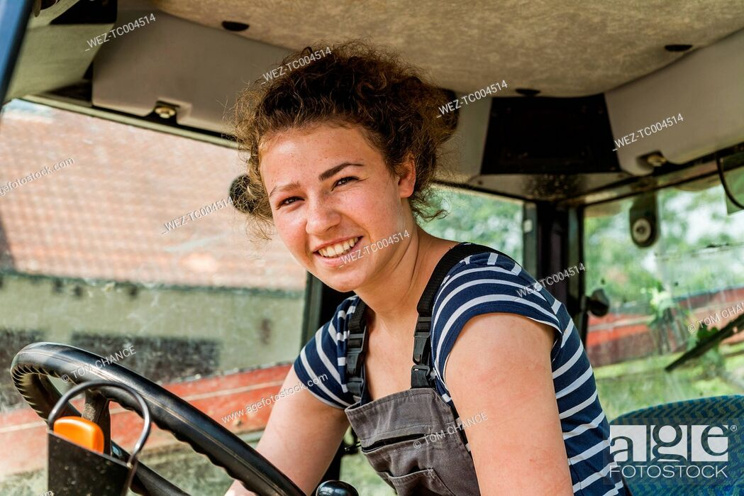 Stock Photo: Portrait of smiling farmwoman in tractor.
