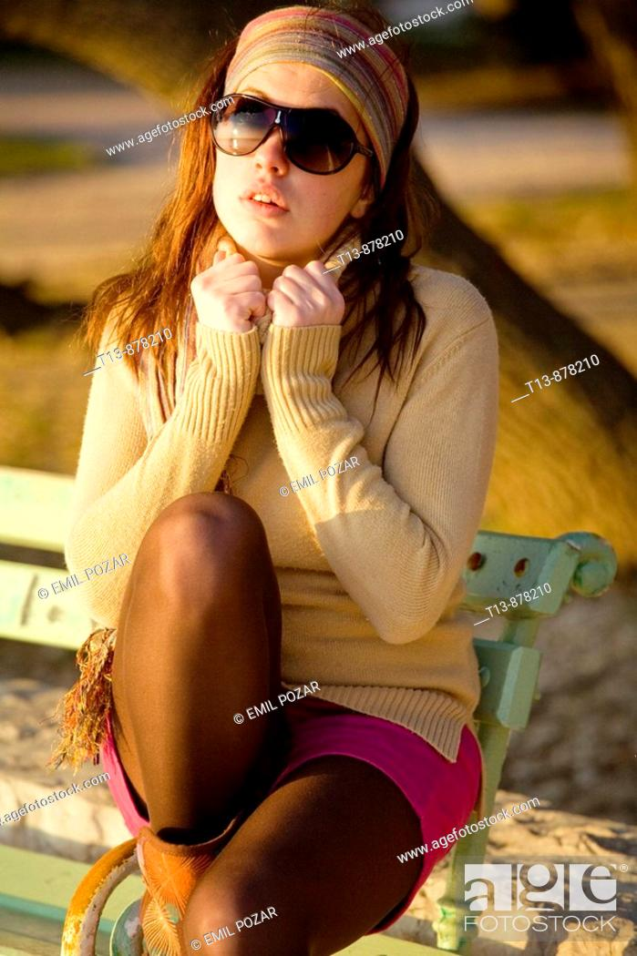 Stock Photo: Sexy young woman with spectacles is sitting on wooden park bench.