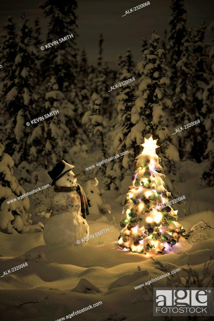 Stock Photo: Snowman stands in a snowcovered spruce forest next to a decorated Christmas tree in wintertime.