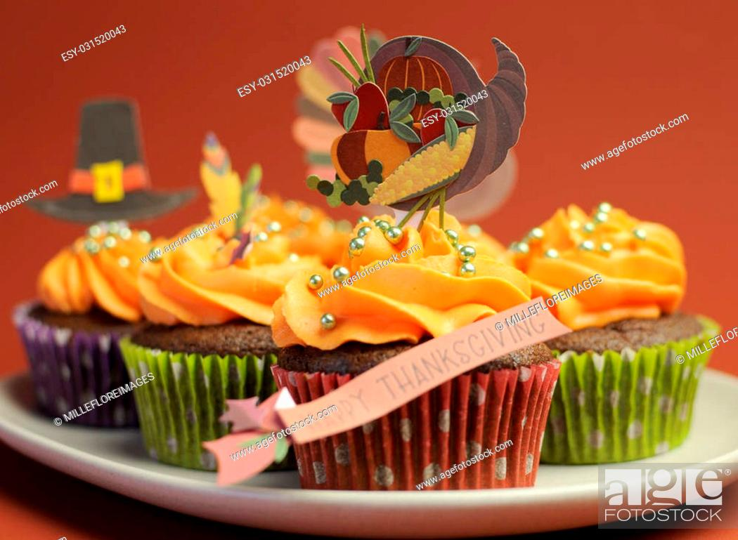 Stock Photo: Happy Thanksgiving cupcakes with turkey, feast, and pilgrim hat topper decorations against a harvest red brown background.