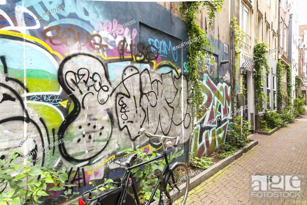 Stock Photo: Netherlands, Amsterdam. Graffiti covers the side of building on a upscale residential street.