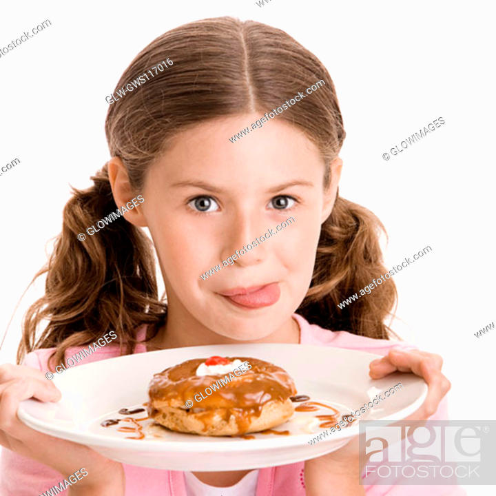 Stock Photo: Portrait of a girl holding a donut in a plate licking her lips.
