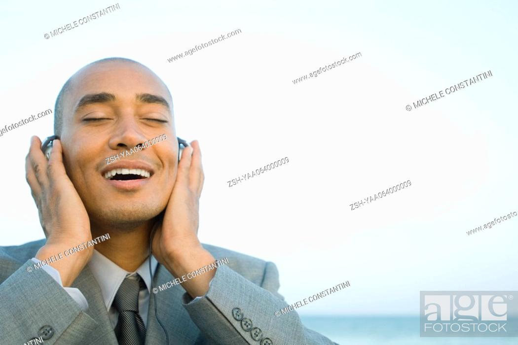 Stock Photo: Businessman listening to headphones outdoors, smiling, eyes closed.