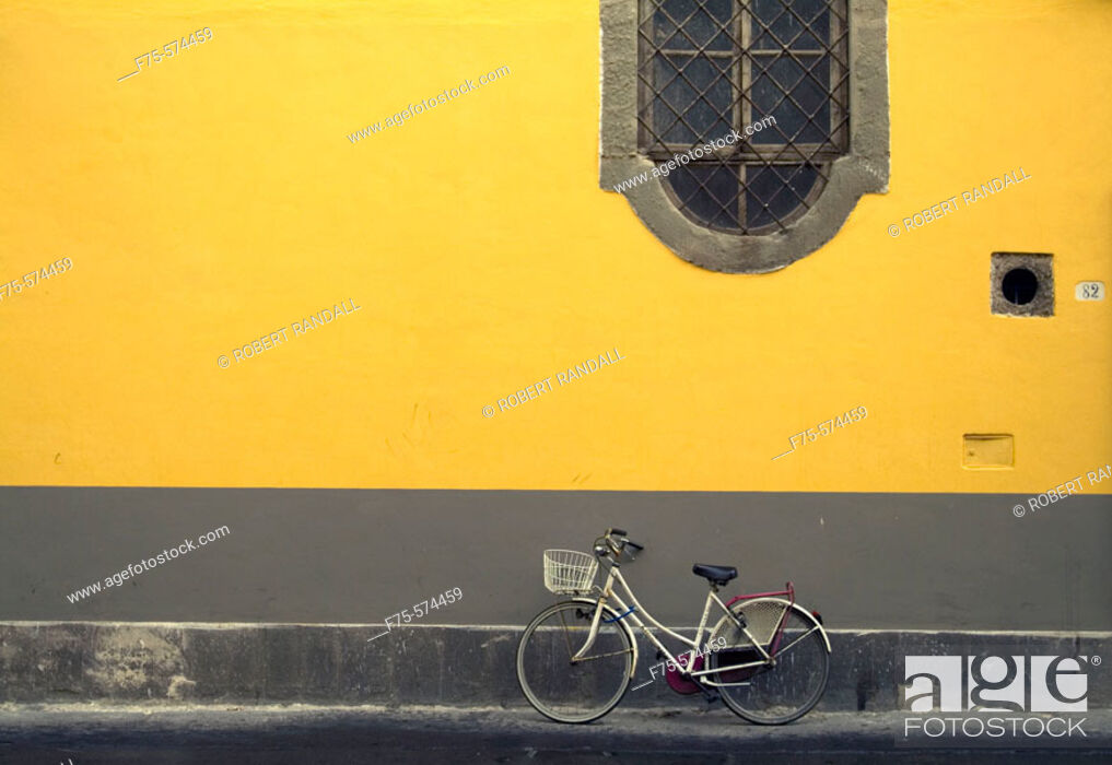 Stock Photo: Bike leaning against a yellow wall in Lucca, Italy.