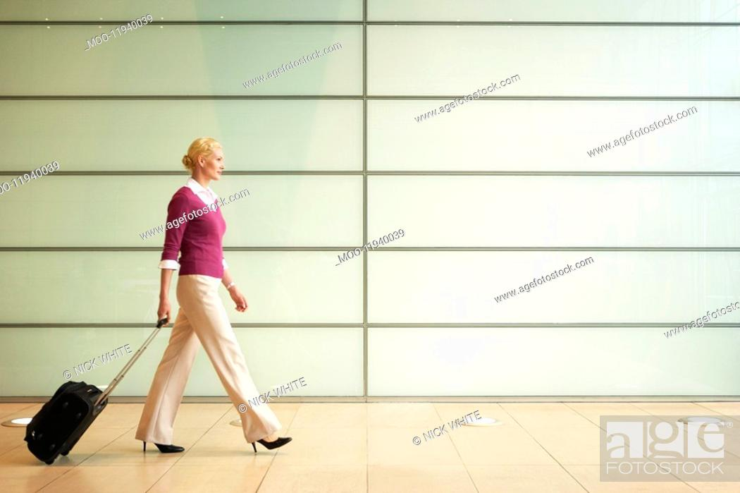Stock Photo: Businesswoman Pulling Carry On Suitcase side view.