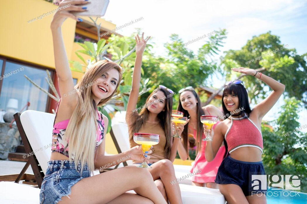 Stock Photo: Young woman taking selfie with friends at the poolside.