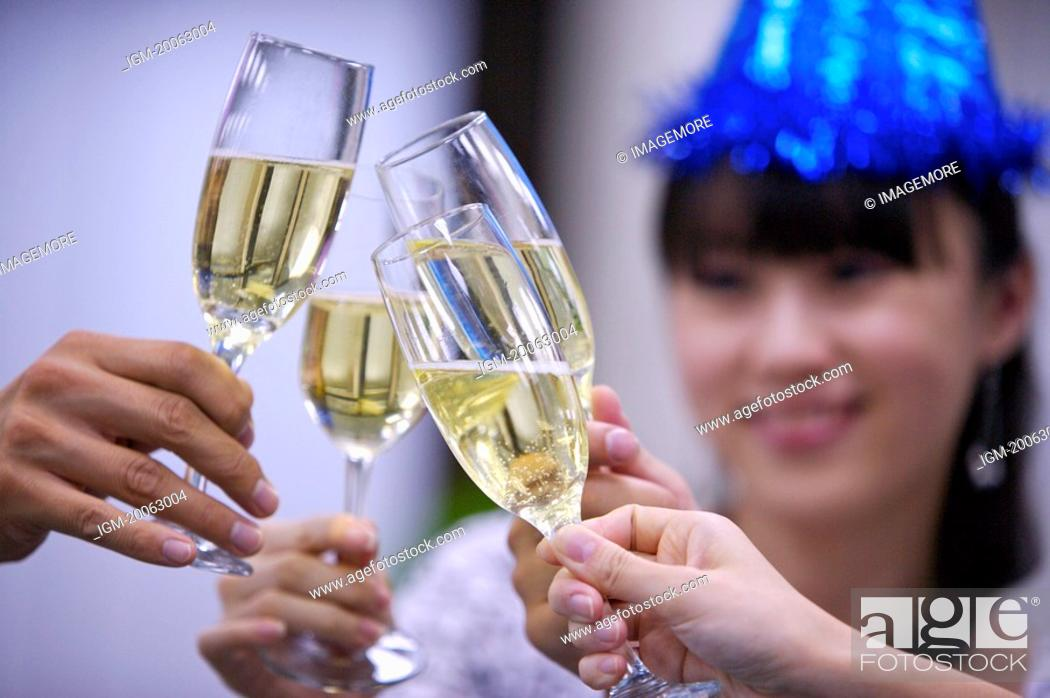 Stock Photo: People holding glasses of champagne to toast together.