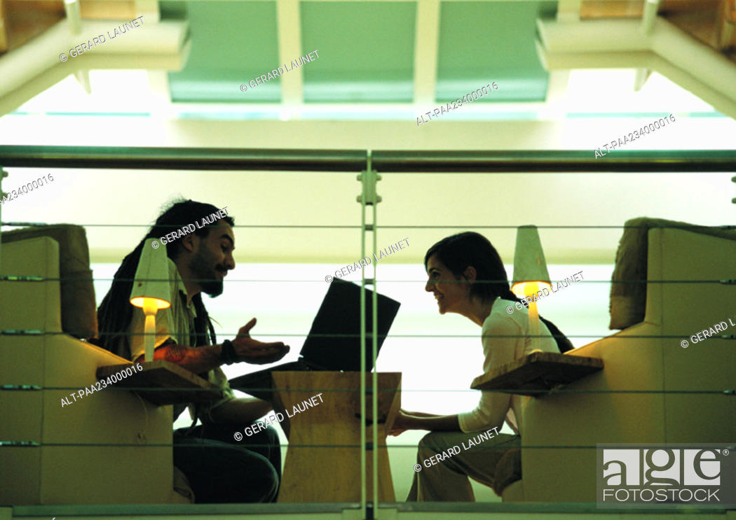 Stock Photo: Man sitting and talking with woman, side view.