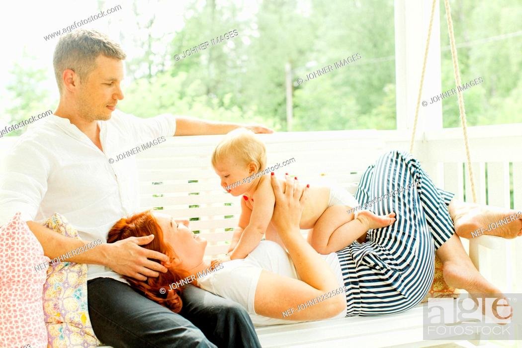 Imagen: Parents with baby boy on swing.