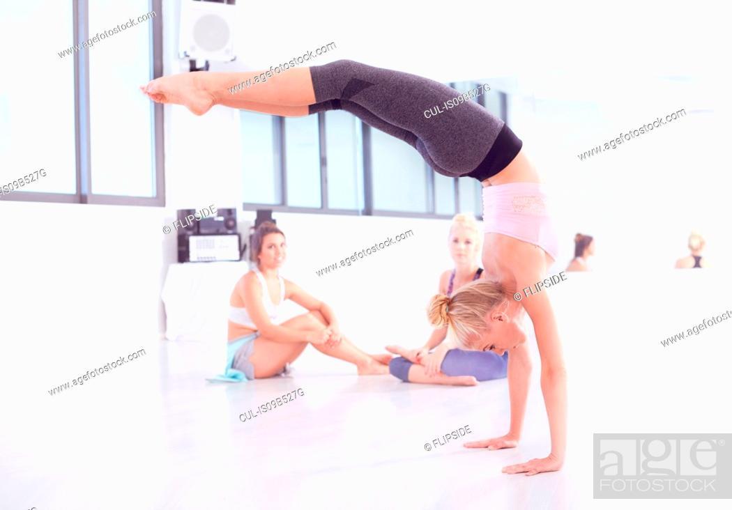 Stock Photo: Young female ballet dancer practicing in dance studio, doing handstand.