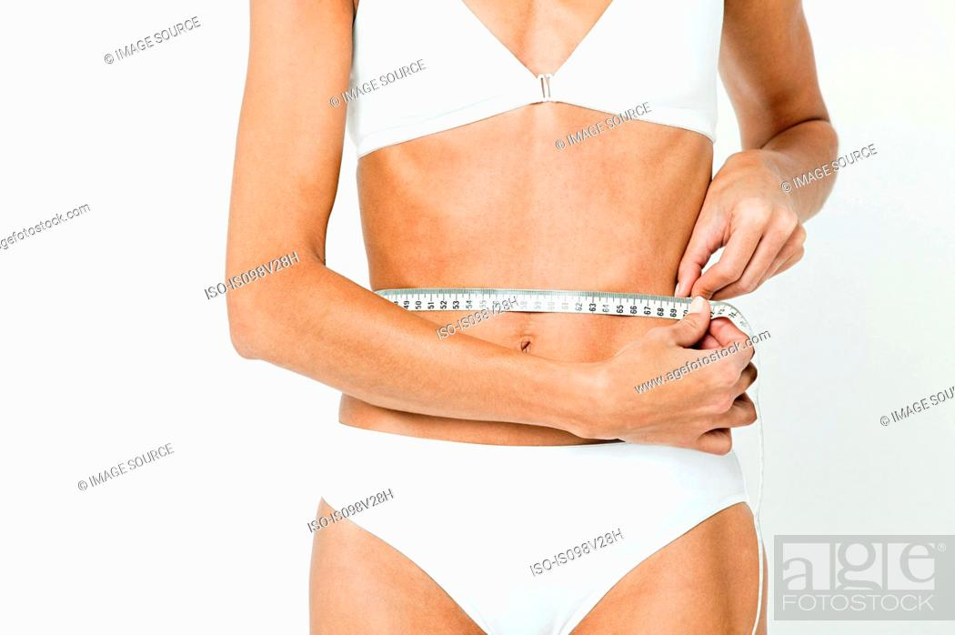 Stock Photo: Young woman measuring waist with tape measure.