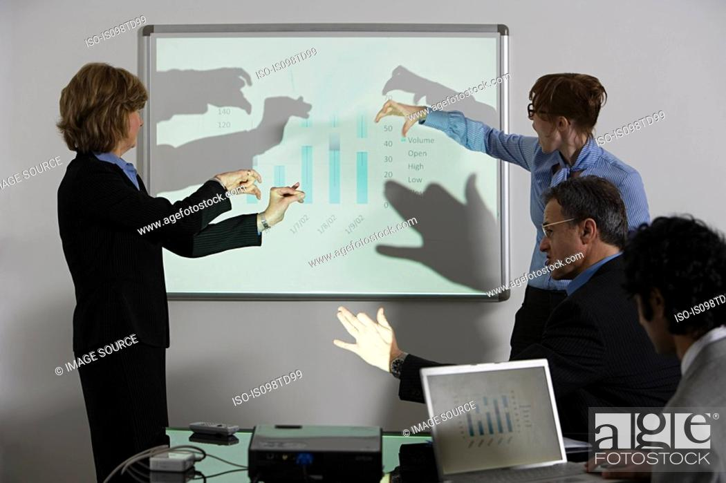 Stock Photo: Businesspeople doing shadow puppets in front of whiteboard.