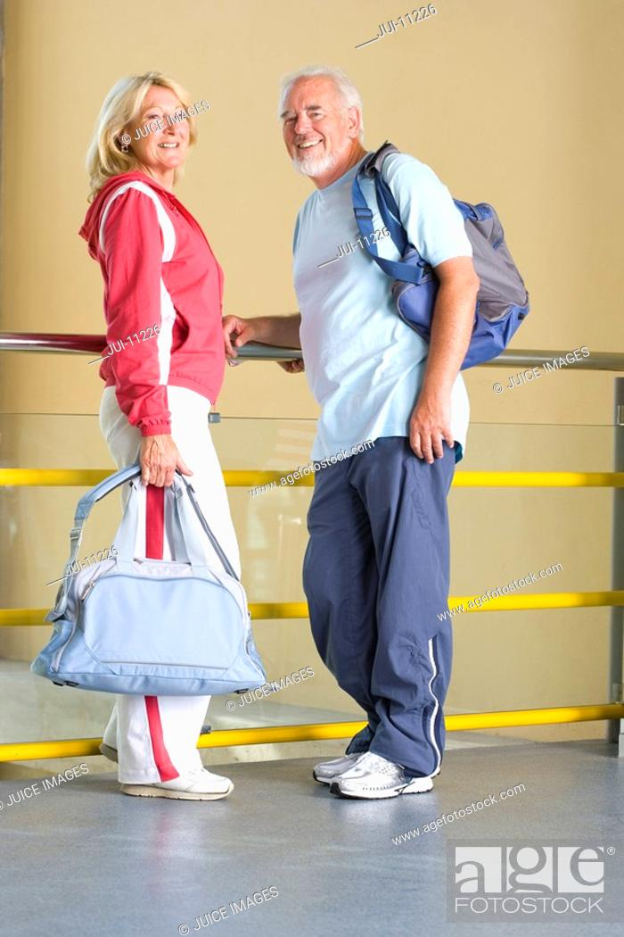 Stock Photo: Senior couple by railing with gym bags, smiling, portrait.