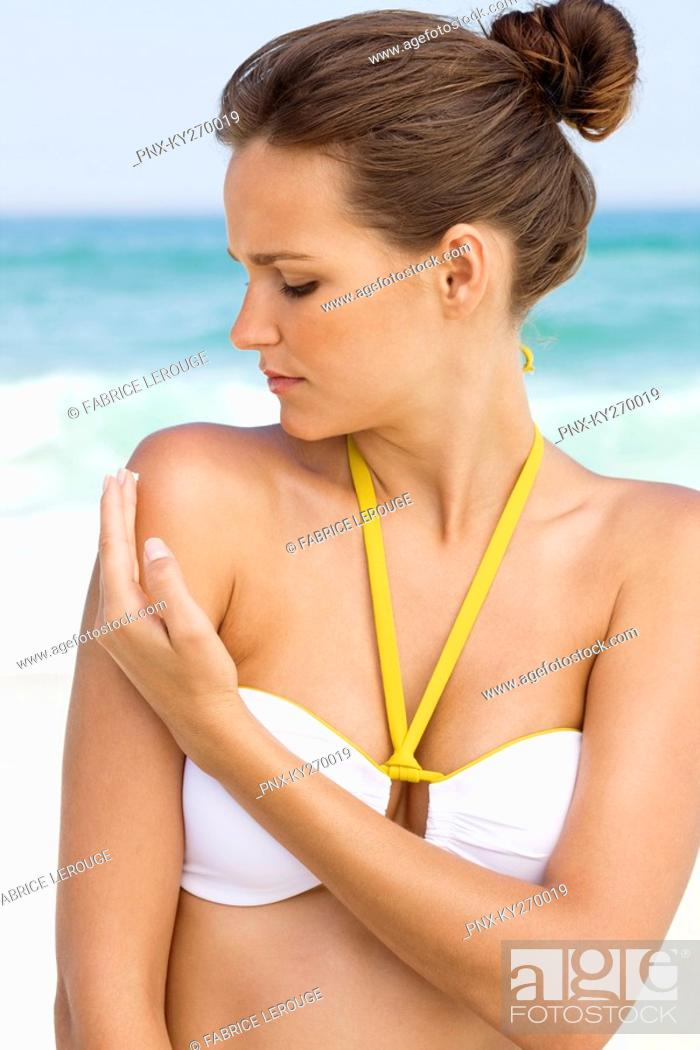 Stock Photo: Woman applying suntan lotion on her shoulder.