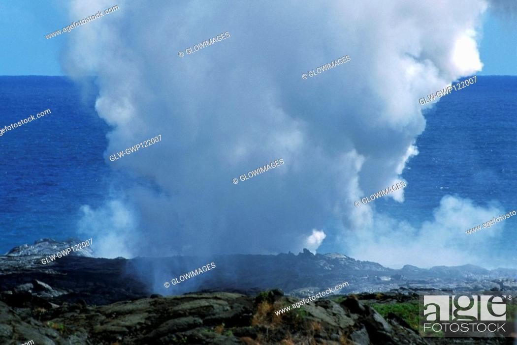 Stock Photo: Steam rises from lava flowing into the sea, Hawaii.