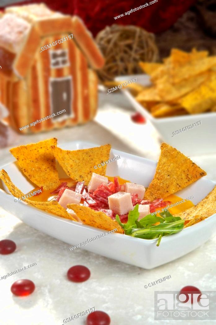 Stock Photo: Nachos Mexican tortilla chips with Cheddar cheese, salami, and chopped cooked ham.