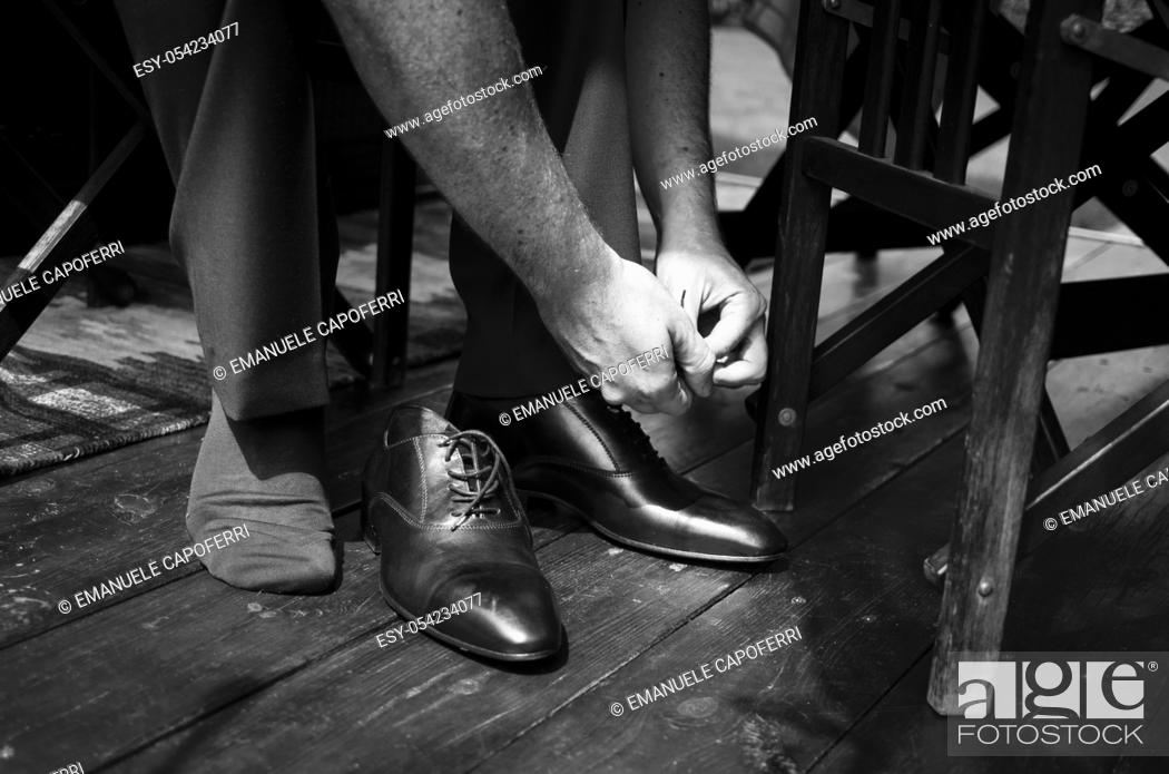 Stock Photo: Hands of groom and shoes.