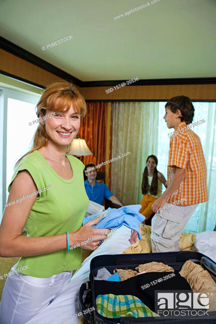 Stock Photo: Portrait of a young woman holding clothes and smiling.
