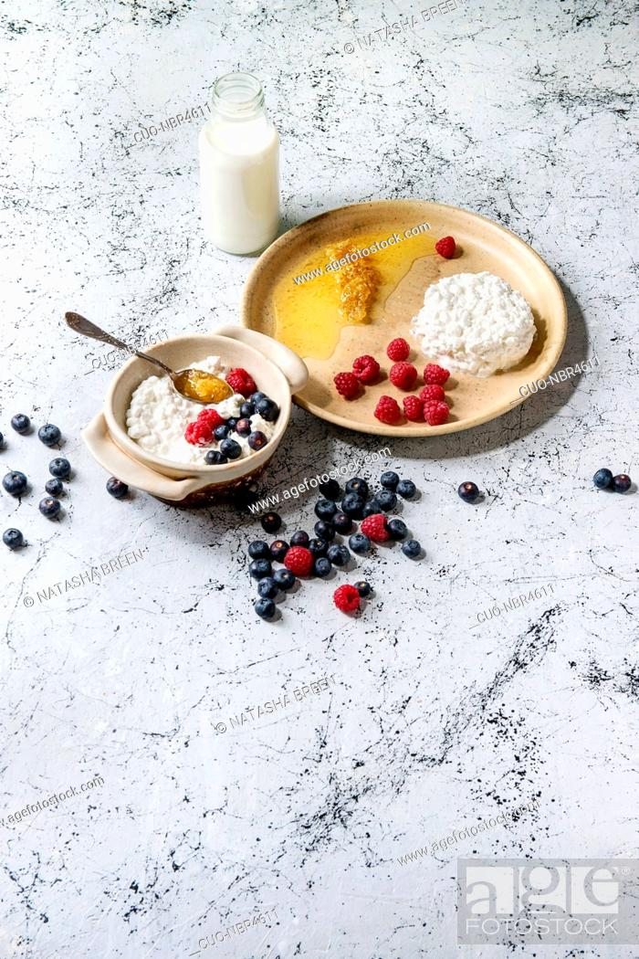 Stock Photo: Ceramic bowl of homemade cottage cheese served with blueberries, raspberries, bottle of milk and honeycombs over white marble texture background.