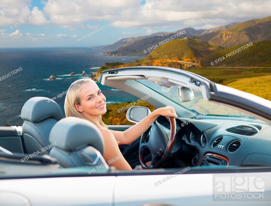 Stock Photo: woman driving convertible car on big sur coast.