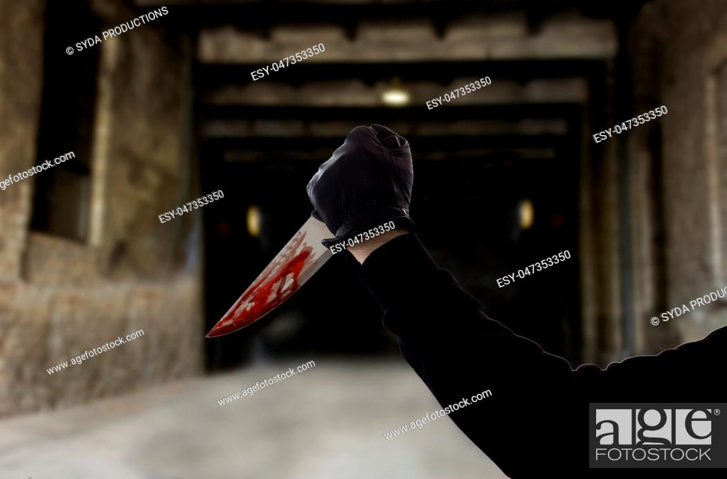 Stock Photo: hand in glove with bloody knife over dark gateway.