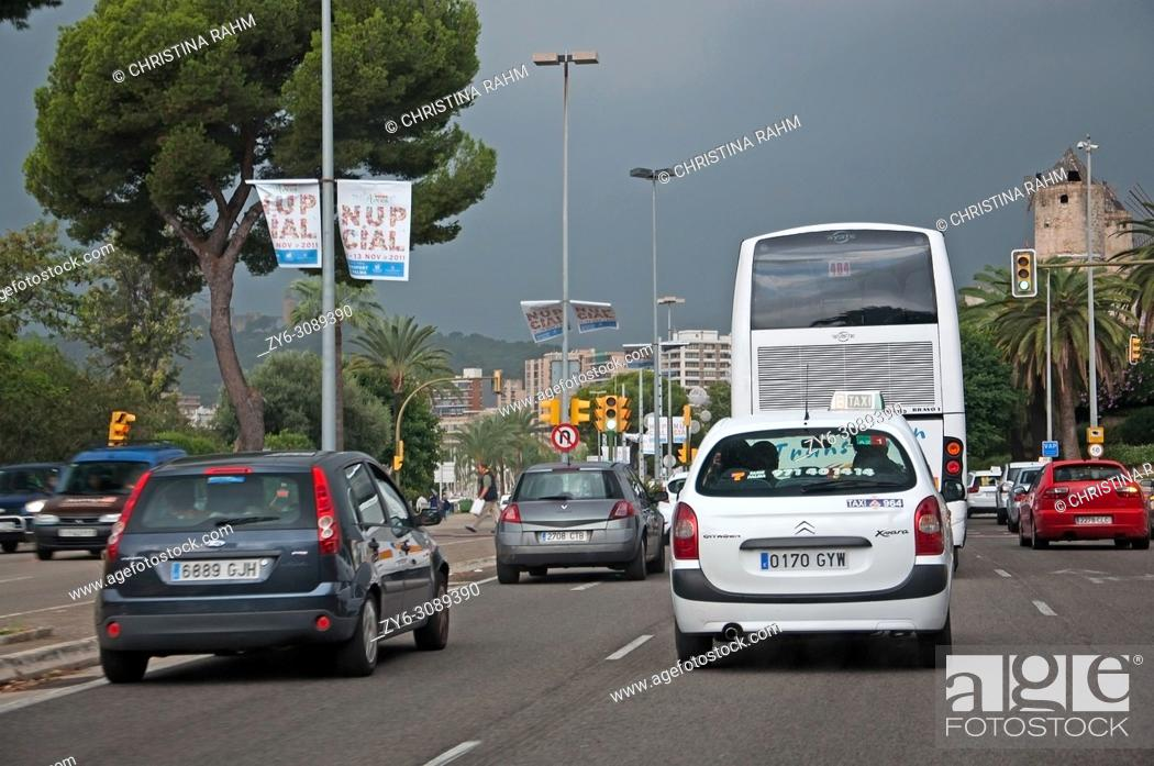 Stock Photo: Rainy winter skies and cars in city traffic with Christmas light fixtures up in November 2011 in Palma de Mallorca, Spain.