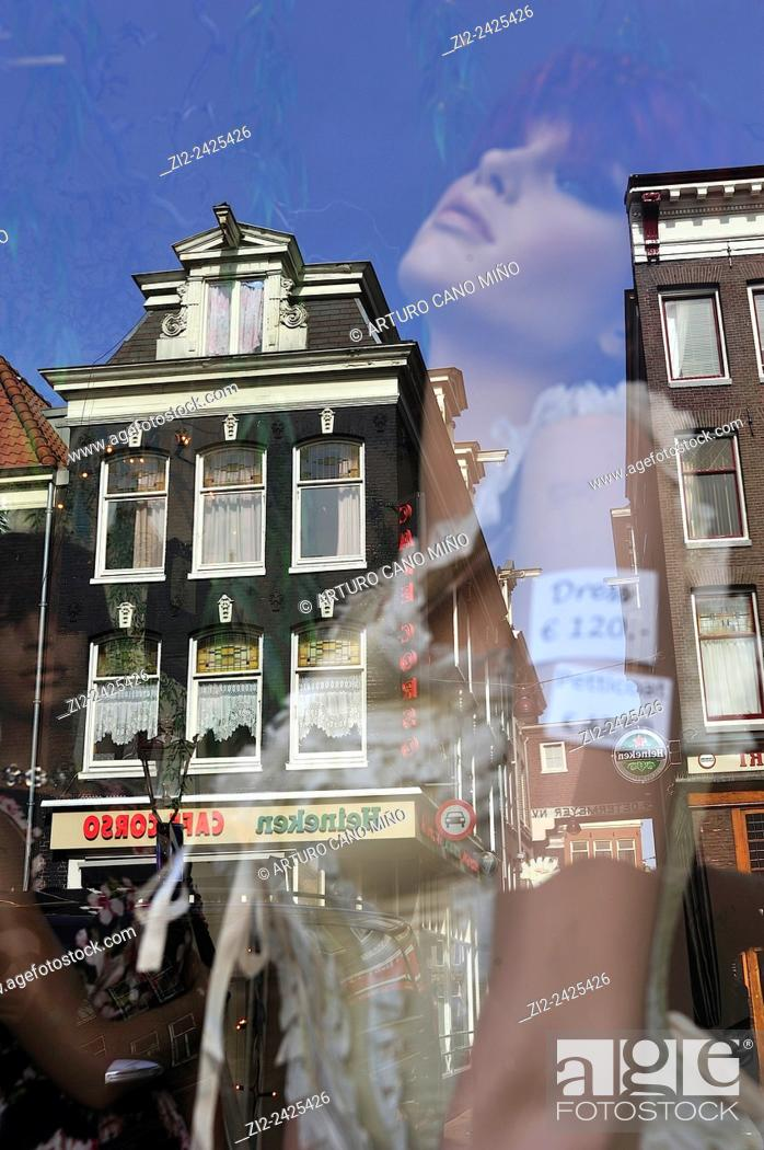 Stock Photo: A mannequin in a shop window with reflection of a building. Amsterdam, The Netherlands.