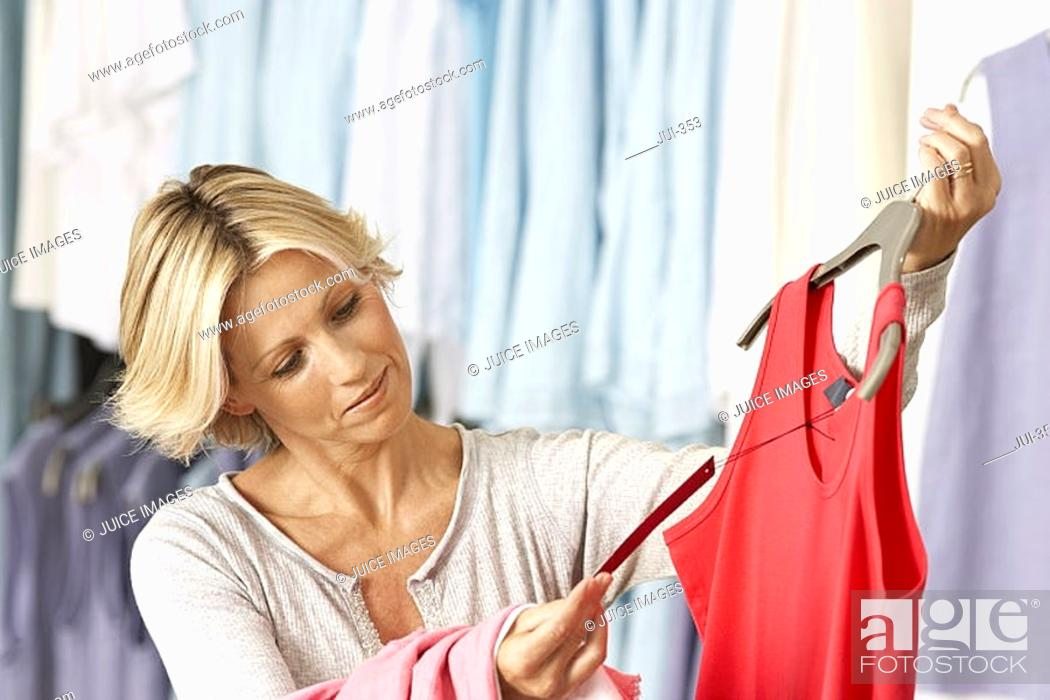 Stock Photo: Mature woman shopping in clothes shop, holding red vest top on coathanger, checking price tag, smiling.