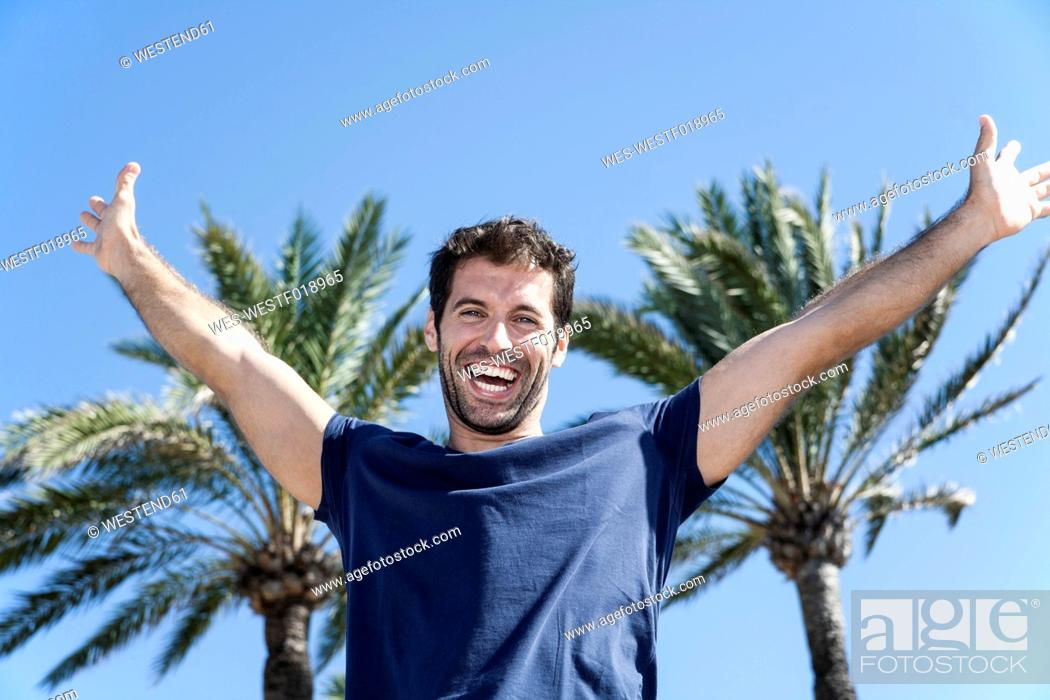 Stock Photo: Spain, Mid adult man pretending to fly against palm tree.