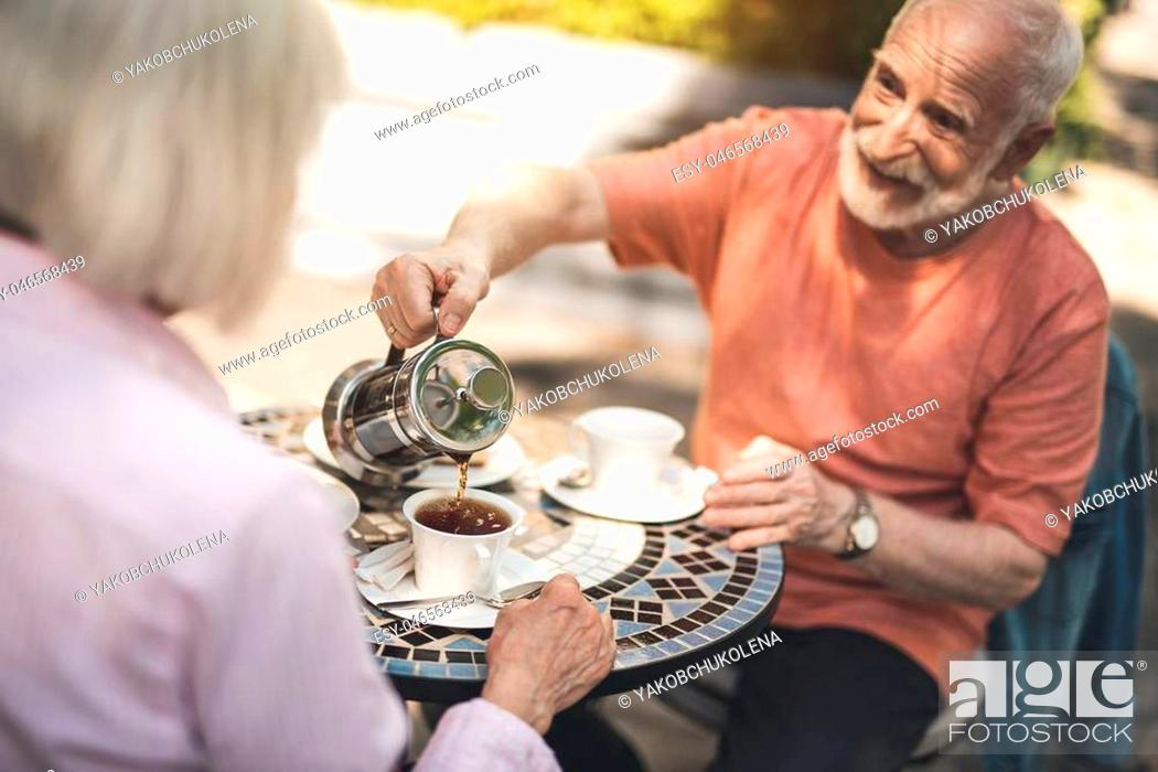 Stock Photo: Here you are. Waist up portrait of happy mature male pouring hot drink into cup while having dinner with wife. They are sitting at table and admiring precious.
