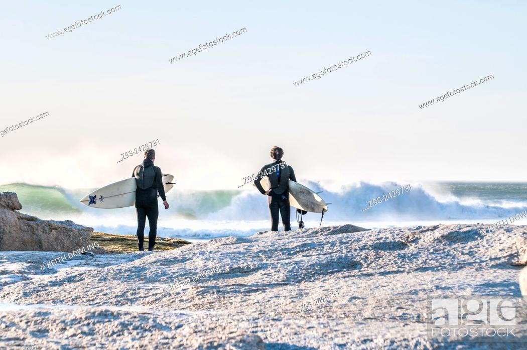Stock Photo: Surfers with boards survey the waves at Noord Hoek beach, Cape Peninsula, South Africa.
