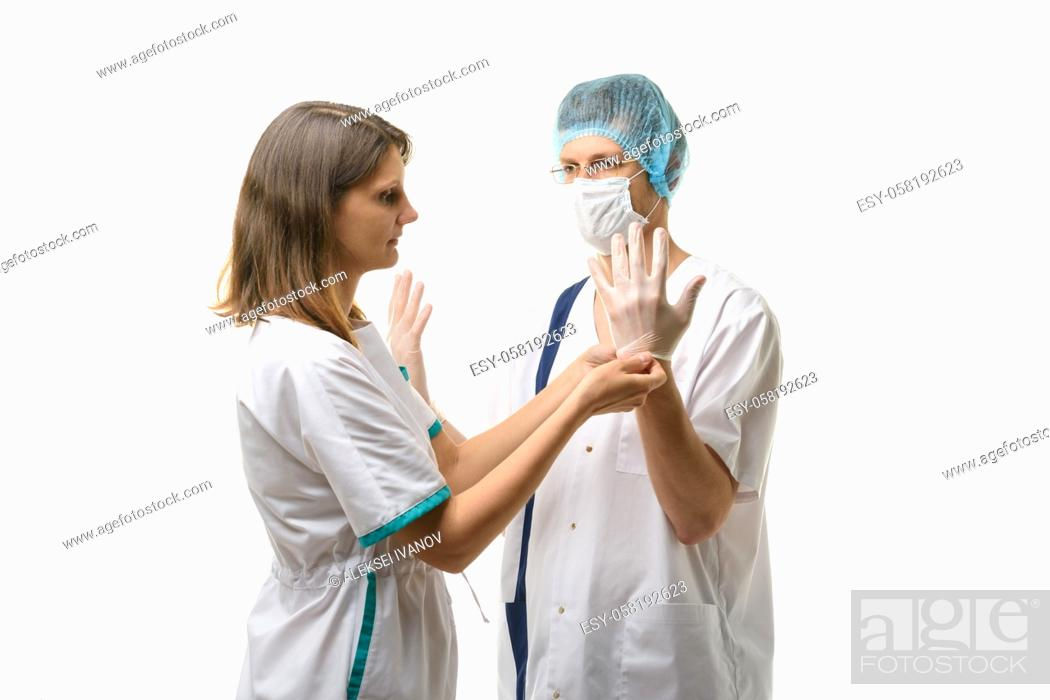 Stock Photo: A nurse puts sterile medical gloves on the surgeon's hands.