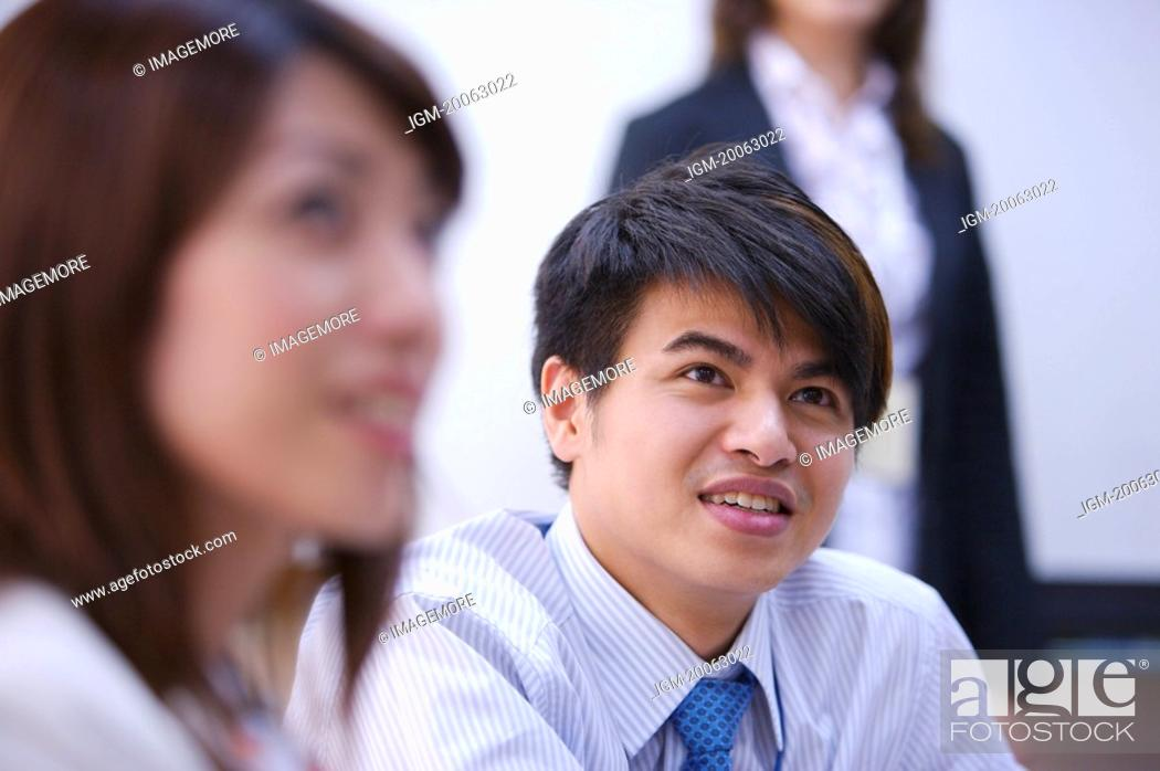 Stock Photo: Young woman and man looking up with smile.